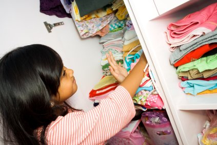 girl in closet adjusting shirts